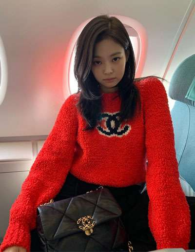 foto jennie blackpink pakai sweater merah dan tas chanel di dalam pesawat terbang